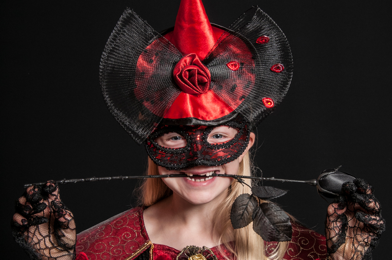 child dressed as Halloween witch isolated on dark background
